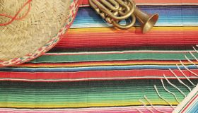 Traditional Mexican fiesta poncho rug in bright colors with sombrero background with copy space