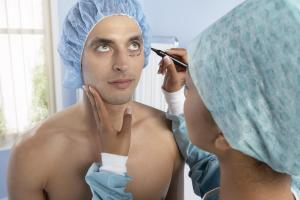 Cosmetic surgeon marking patient's face for surgery