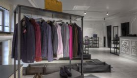 Suits and shoes on rack in clothing store for men