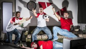 Four young adult men friends watching football on television: Goal