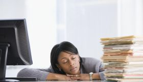 African American businesswoman sleeping at desk