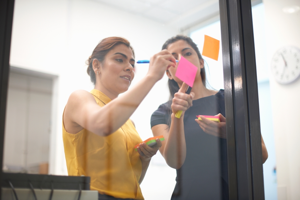 Two businesswomen writing out sticky notes on office glass wall