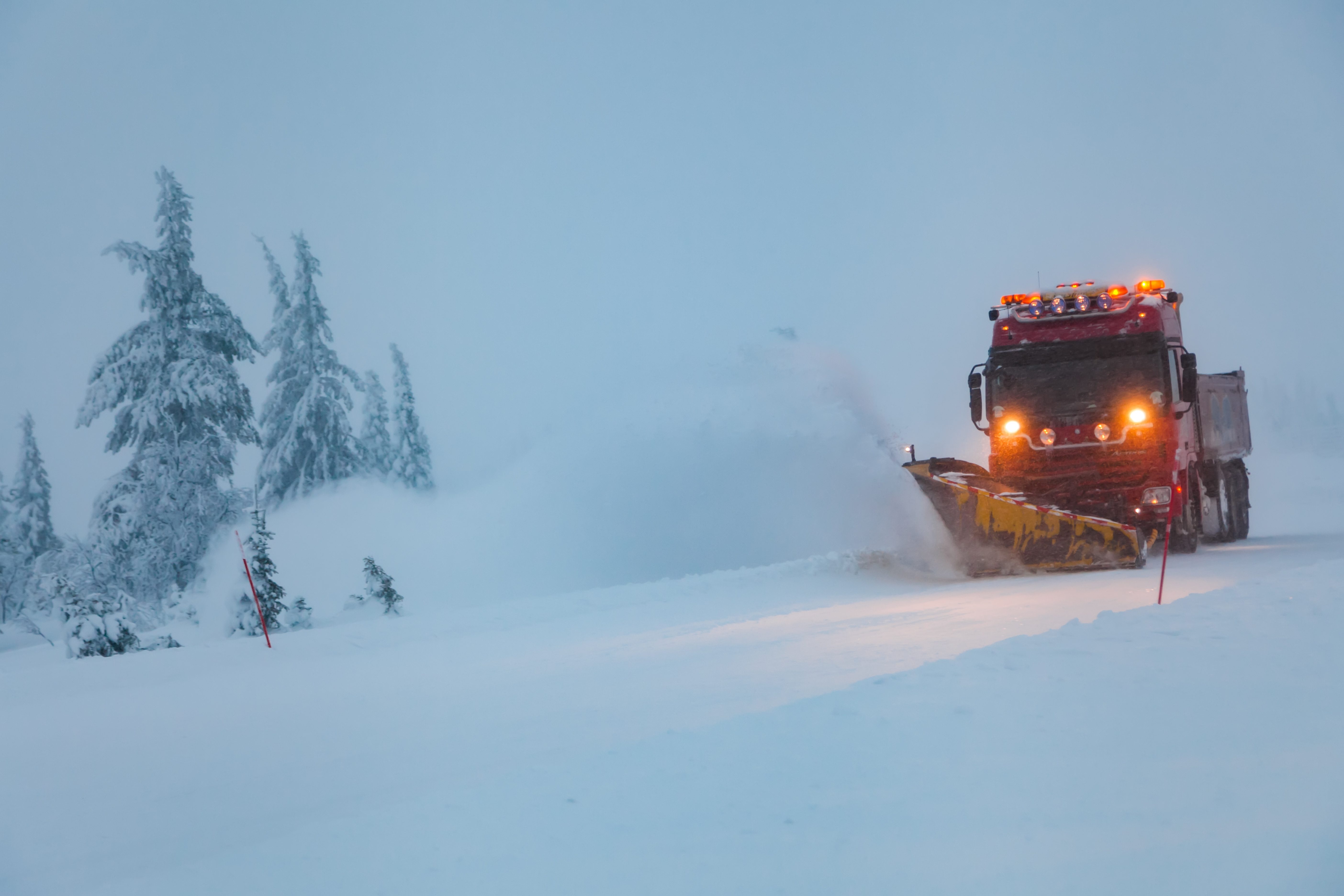 Snowblower grader clears snow covered country road