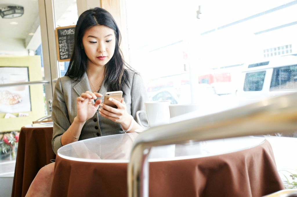 Asian businesswoman texting on cell phone