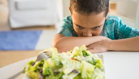 Mixed race boy refusing to eat salad