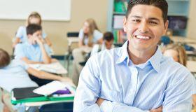 Confident Hispanic private school teacher in classroom