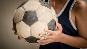 Midsection Of Boy Standing With Soccer Ball Against Wall