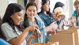 Volunteers pack canned food in community food drive
