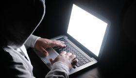 hooded hacker stealing data from laptop