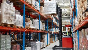Warehouse logistic center. Worker driving on a forklift