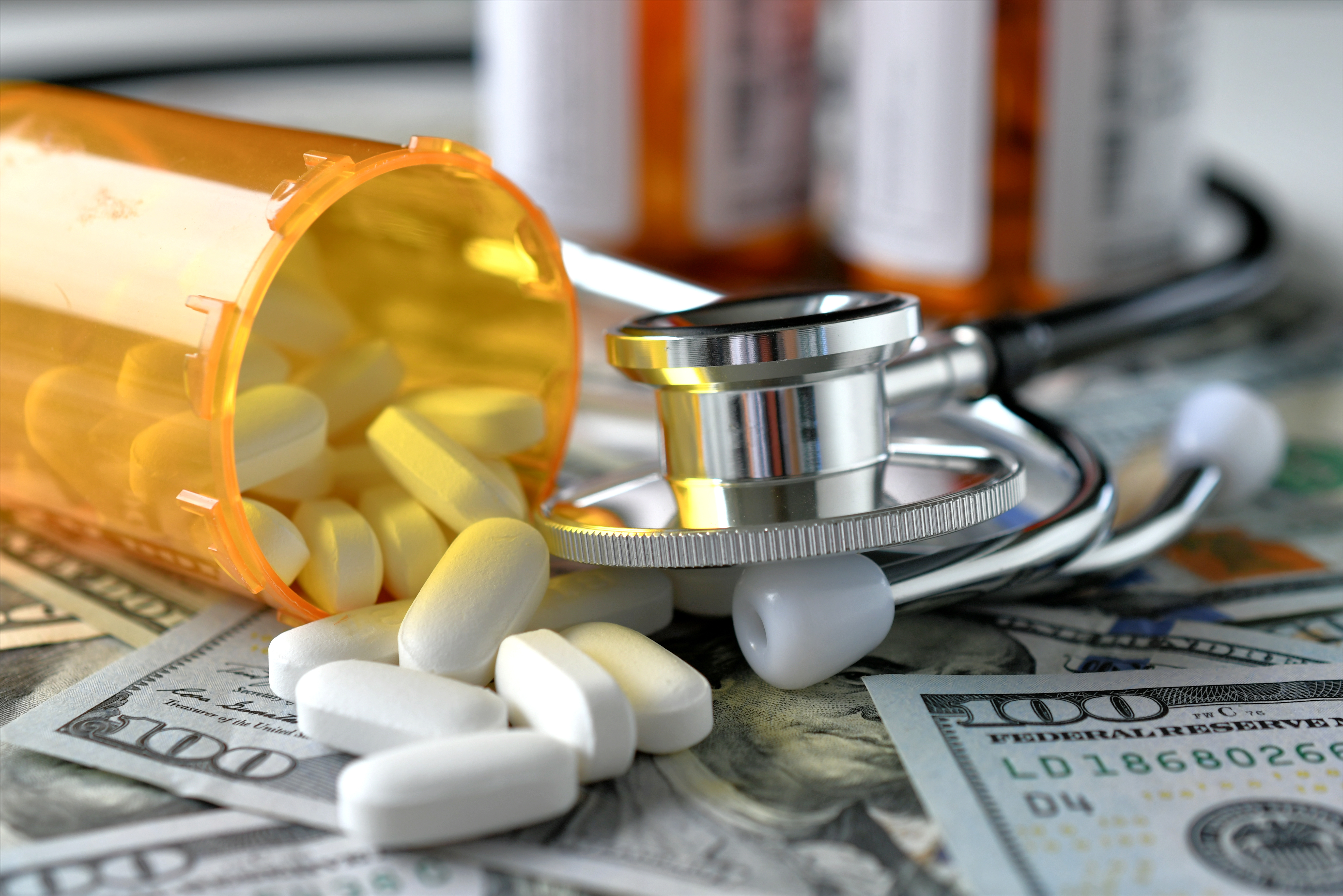 High Angle View Of Medicines With Stethoscope And Paper Currencies On Table