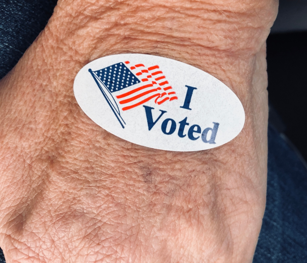"""Senior woman's hand displaying """"I voted"""" sticker after early voting"""
