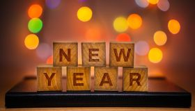 New Year Text on Wood Block Against Abstract Colorful Illuminated Defocused Bokeh Lights Background.