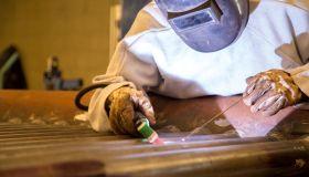Man Welding Metal At Workshop