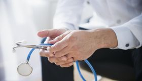 Mixed race doctor's hands holding stethoscope