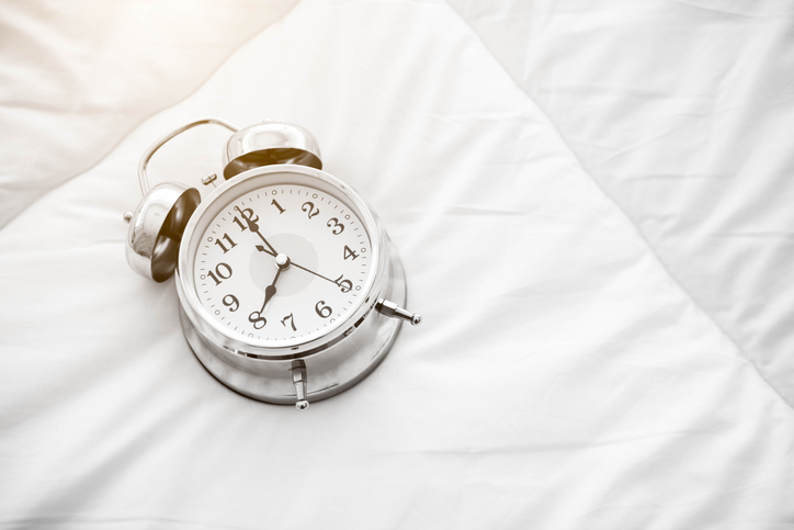 High Angle View Of Alarm Clock On Bed