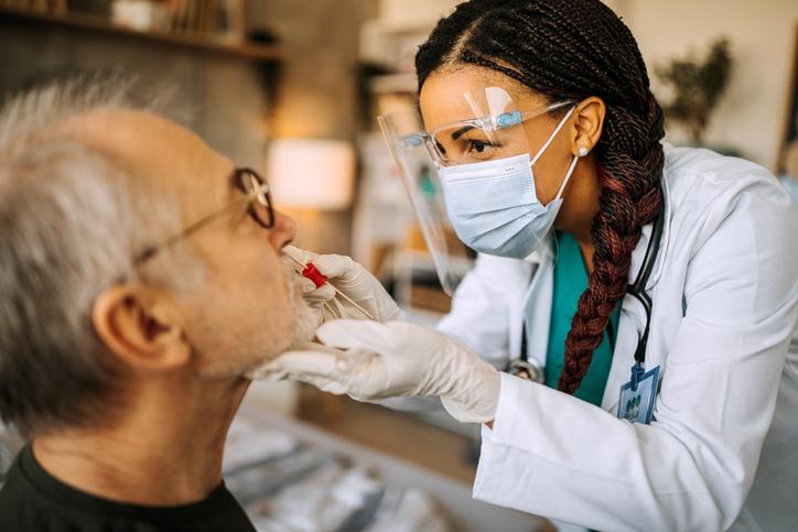 Nurse taking swab test from senior man patient during home visit