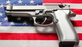 Stainless steel 9 mm caliber handgun laying on an American flag background - part of a series