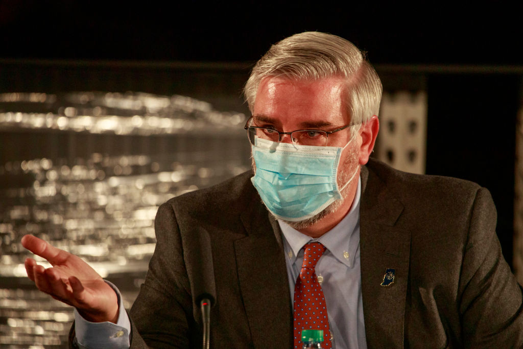 Indiana Governor Eric Holcomb wearing a face mask speaks...