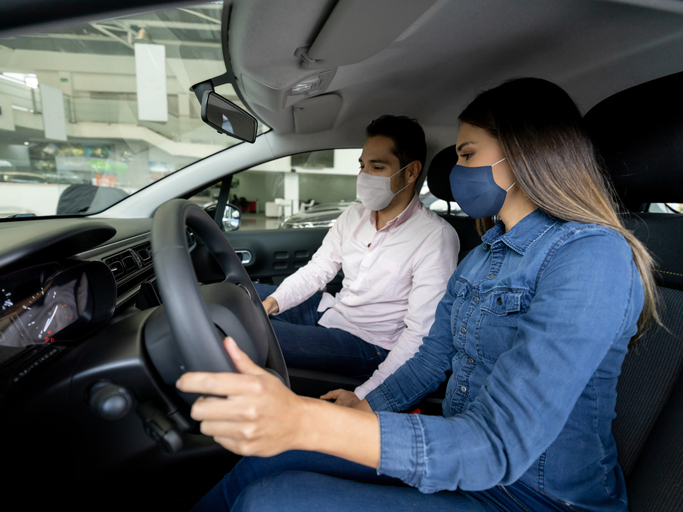 Woman talking to a salesman and wearing facemasks while buying a car at the dealership