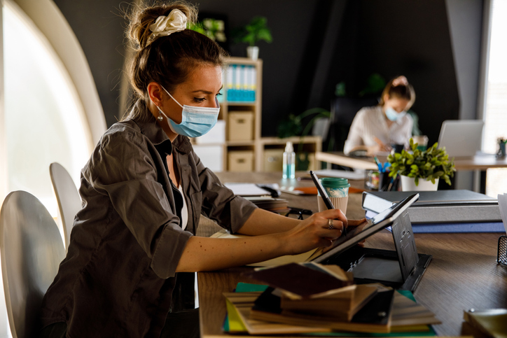 Graphic designer sitting at her desk and using graphics tablet