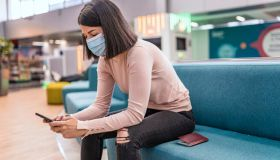 Young woman using mobile phone in the airport.