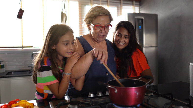 Grandmother cooking with granddaughters at home