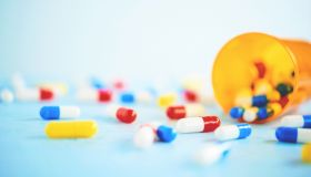 Medical Themed Background with a Variety of Pills on Blue Table