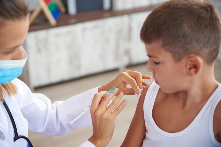 a pediatrician vaccinates a little boy in a pediatric clinic