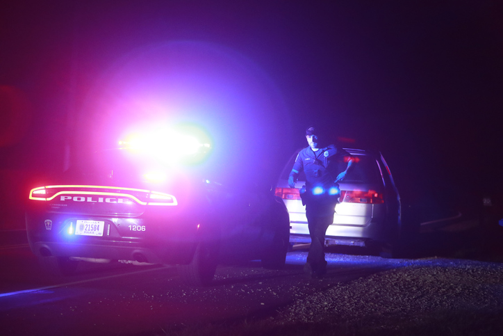 A police officer walks back towards a police car at the scene of a traffic stop